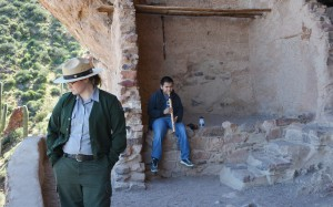 Jordan Jarrett, an archaeologist at Tonto National Monument, watches visitors make their way up the Lower Cliff Dwelling trail as Robert Wilson Jr. performs on his flute during Heritage Days, March 12. Wilson has performed at the annual event for 10 years.